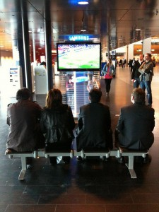 Four people in front of a television in Stockholm Airport